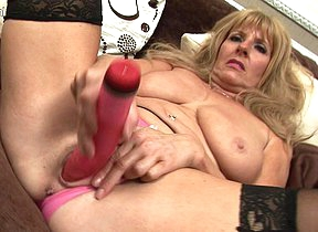 Sexy mature redhead stuffing her pussy with a dildo